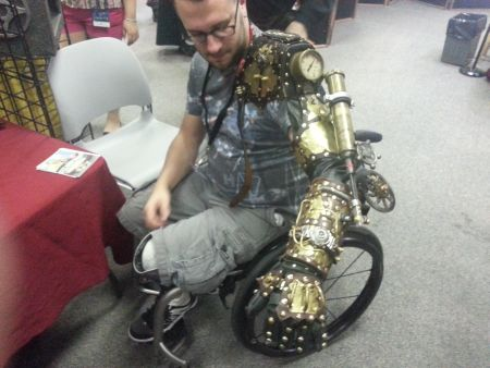 Steampunk arm. The guy really was in a wheel chair because he had a prosthetic leg!
